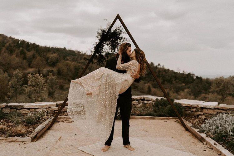 Bearded Groom in Black Outfit Picking Up his Bride in Shimmering Gold Wedding Dress in Front of Triangle Frame