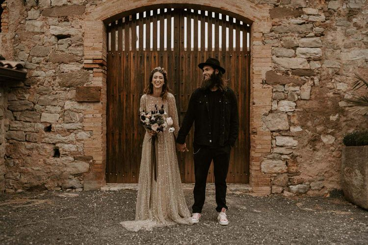 Bride in Shimmering Gold Wedding Dress Holding Wedding Bouquet Tied with Ribbons and Groom in Black Outfit and Fedora Hat