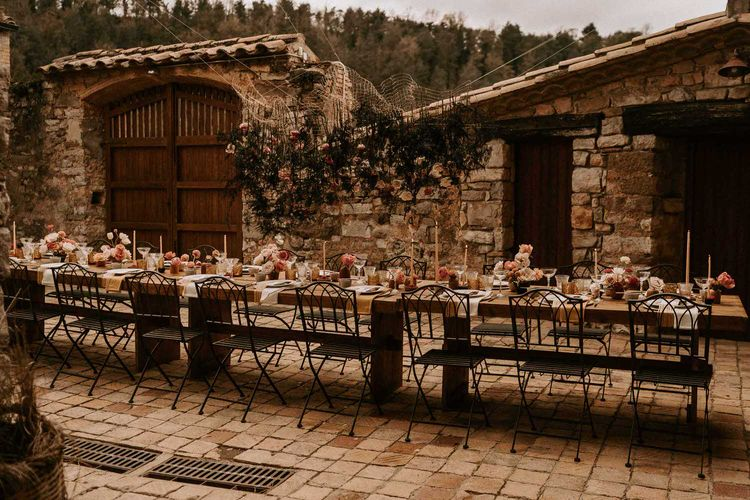 Outdoor Wedding Reception with Hanging Floral Installation and Centrepieces