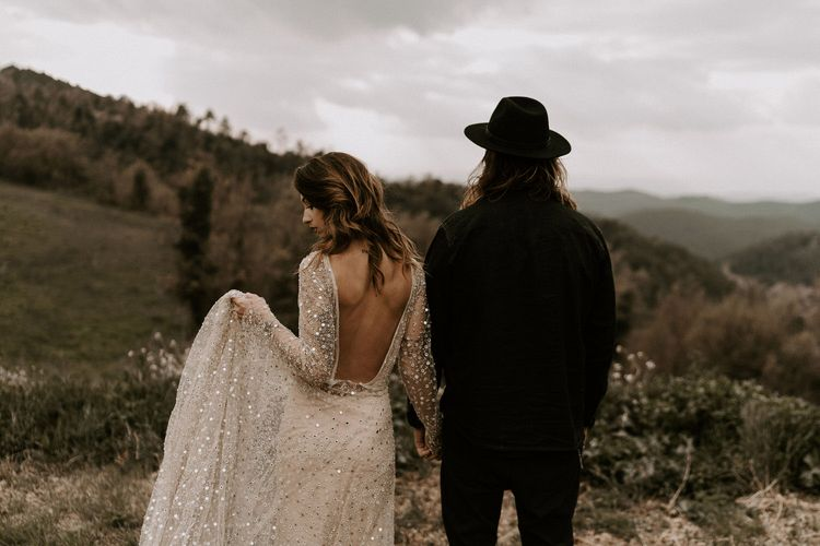 Bride in Backless Gold Sequin Wedding Dress and Groom in Black Fedora Hat Overlooking The Spanish Mountains