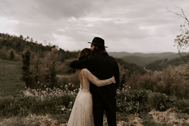 Bride in Backless Gold Sequin Wedding Dress and Groom in Black Fedora Hat Embracing