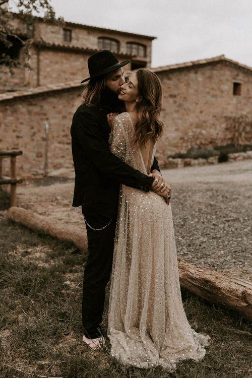 Bride in Backless Gold Sequin Wedding Dress and Groom in Black Fedora Hat Hugging
