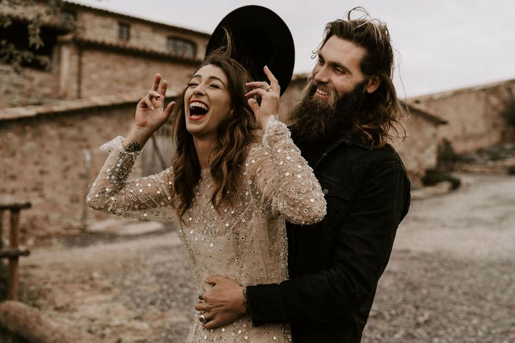 Bride in Gold Sequin Wedding Dress and Groom in Black Fedora Hat Laughing