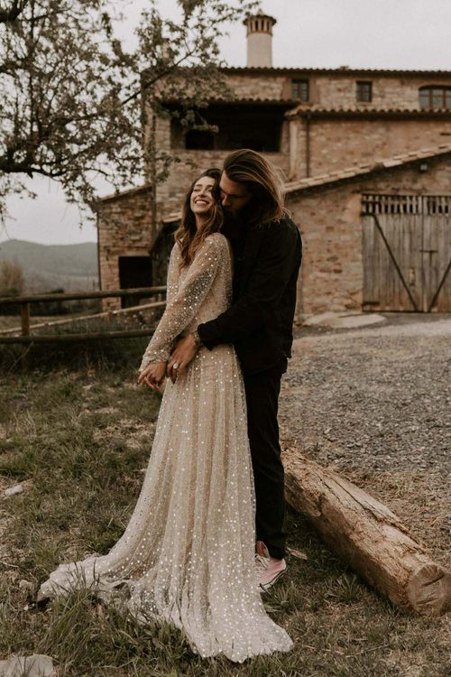 Bride in Gold Sequin Wedding Dress and Groom in Black Hugging at This Must Be The Place Barcelona Wedding Venue