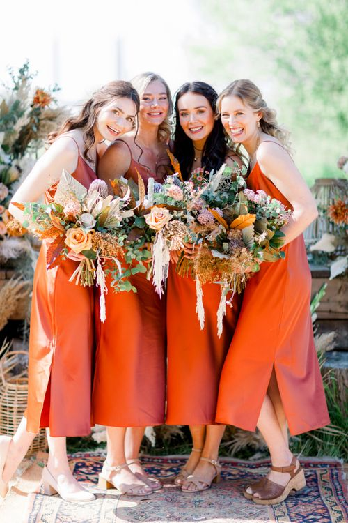 Bridesmaids in Burnt Orange Bridesmaids Dresses with Dried Flower Bouquets