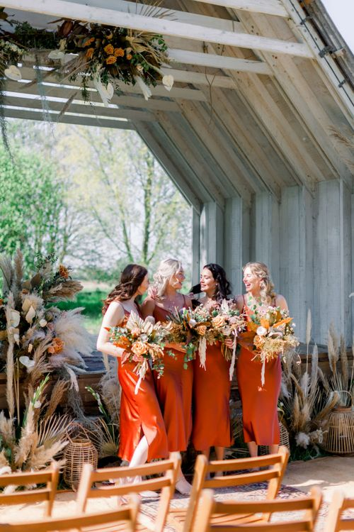 Bridesmaids in Burnt Orange Bridesmaids Dresses with Dried Flower Bouquets Standing in Front of the Wooden Ceremony Hut