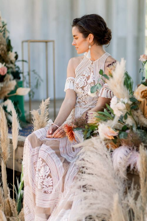 Bride in Rue de Seine Boho Wedding Dress with Tassel  Arm Cuffs Sitting amongst Dried Flower Arrangements
