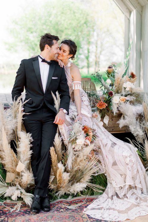 Bride in Rue de Seine Boho Wedding Dress and Groom in Tuxedo Sitting amongst Dried Flower Arrangements