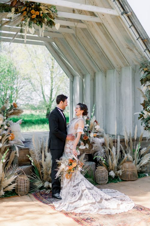 Bride in Rue de Seine Boho Wedding Dress and Groom in Tuxedo Laughing with Dried Flower Arrangements and Moroccan Rugs Ceremony Decor