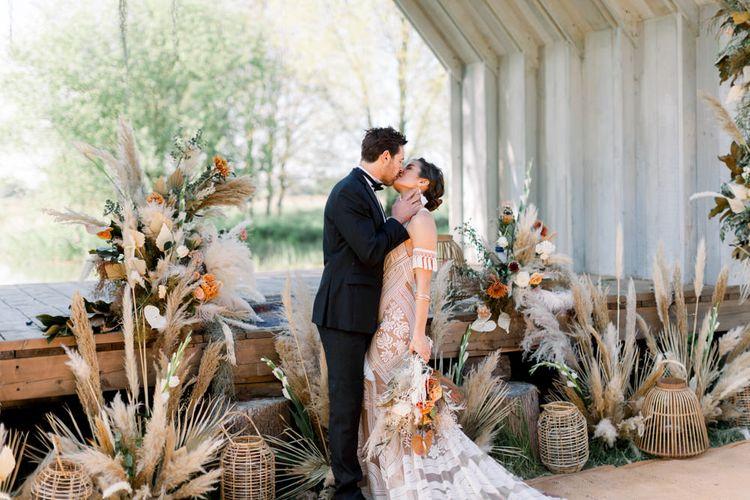 Bride in Rue de Seine Boho Wedding Dress and Groom in Tuxedo Kissing at their Dried Flower Altar