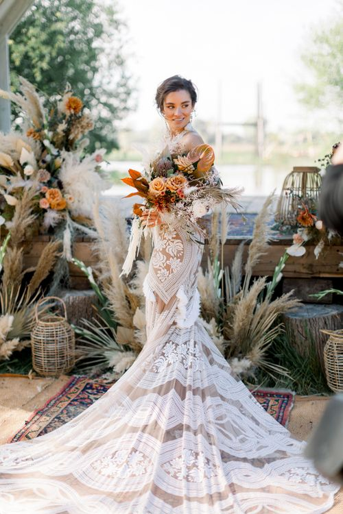 Bride in Rue de Seine Boho Wedding Dress with Orange Protea Bridal Bouquet