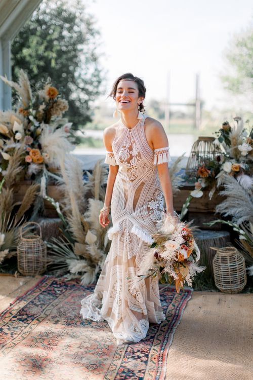 Laughing Bride in Rue de Seine Boho Wedding Dress with Orange Protea Bridal Bouquet