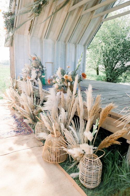 Pampas Grass Stems in Wicker Baskets Decorating the Outdoor Wedding