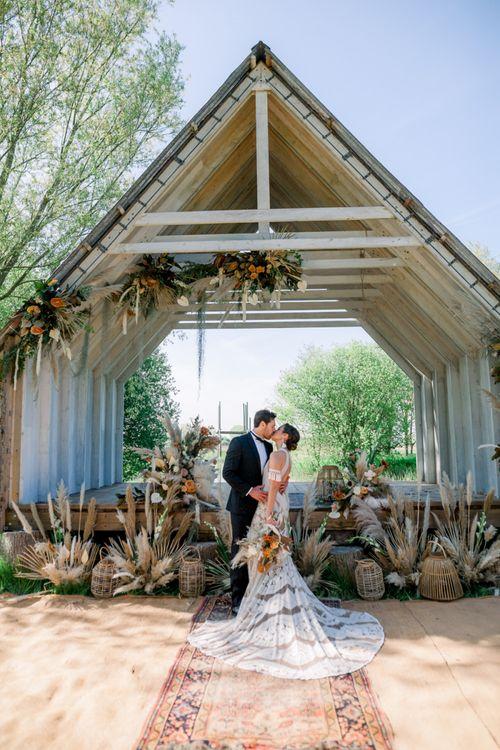 Bride in Rue De Seine Boho Wedding Dress and Groom in Tuxedo Kissing at Their Wooden Hut Outdoor Wedding Ceremony