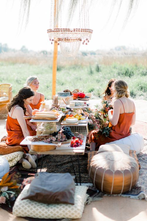 Bridesmaids in Rust Coloured Dresses Enjoying a Grazing Table on Moroccan Pouffe Under a Naked Tipi
