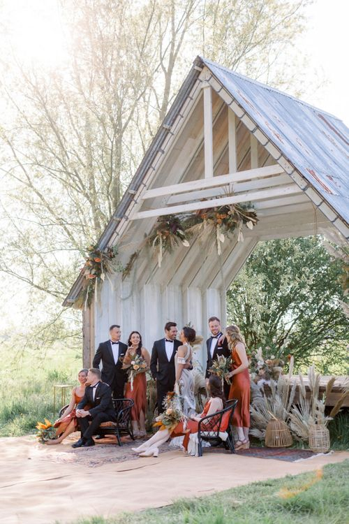 Wedding Party Portrait with Bridesmaids in Rust Dresses, Groomsmen in Tuxedos and Bride in Rue De Seine Boho Wedding Dress