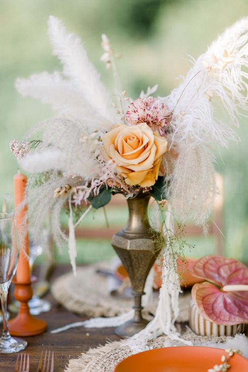 Pampas Grass and Orange Rose Flowers in Gold Vase as Table Centrepiece