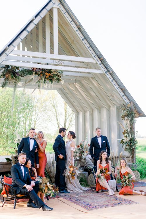 Wedding Party Portrait with the Dried Flower Decorated Ceremony Hut as the Backdrop
