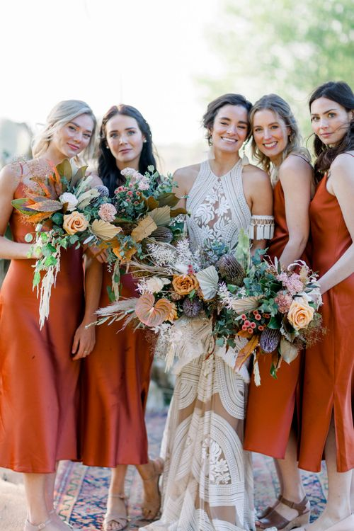 Bridal Party Picture with Bride in Rue De Seine Boho Wedding Dress and Bridesmaids in Rust Coloured Dresses