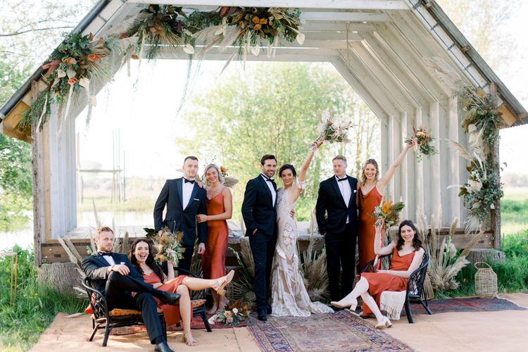 Wedding Party Portrait at the Wooden Ceremony Hut Covered in Dried Flower Arrangements