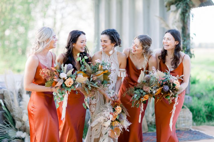 Laughing Bridal Party Picture with Bride in Rue De Seine Boho Wedding Dress and Bridesmaids in Rust Coloured Dresses