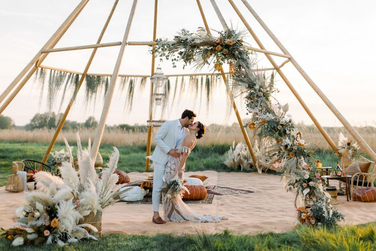 Bride in Rue De Seine Boho Wedding Dress and Groom in Light Suit Kissing in Front of a Naked Tipi Chillout Area