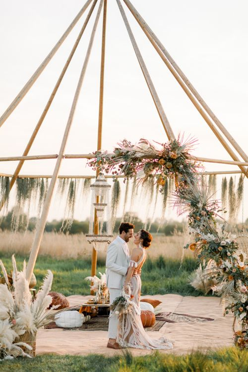 Bride in Rue De Seine Boho Wedding Dress and Groom in Light Suit Laughing in Front of a Naked Tipi Chillout Area