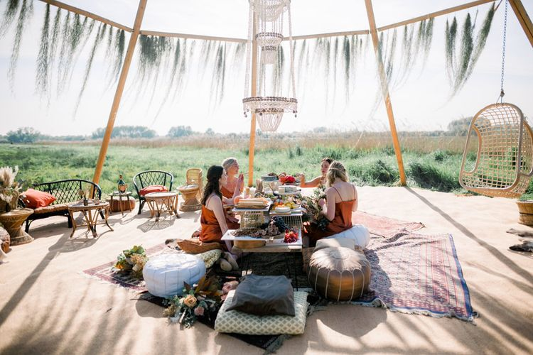 Bridesmaids in Rust Coloured Dresses Enjoying a Grazing Table Under a Naked Tipi