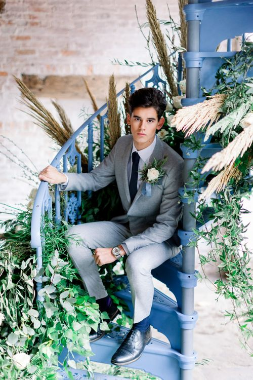 Groom in Grey Suit Sitting on Blue Spiral Staircase