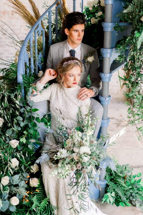 Bride and Groom Sitting on a Blue Spiral Staircase Surrounded by Winter wedding Flower