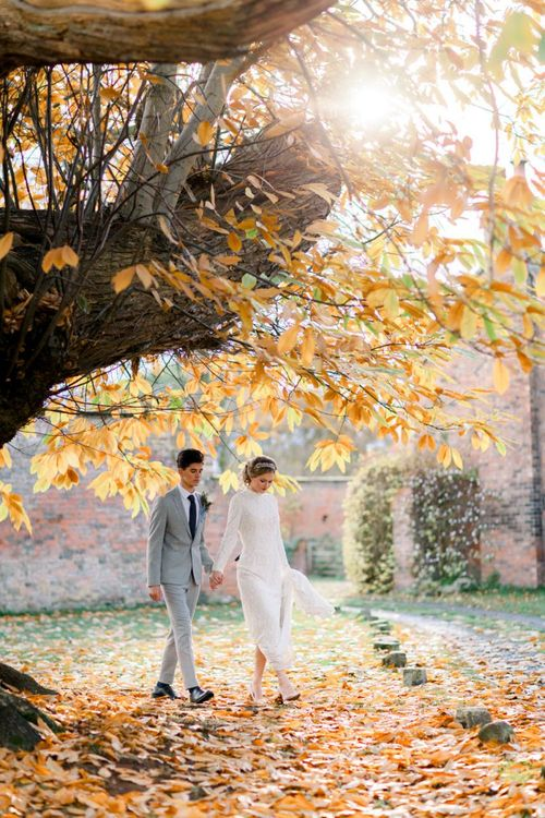 Bride and Groom Holding Hands Amongst the Fallen Autumn Leaves