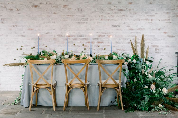 Winter Wedding Table with Wooden Chairs, Blue Linen and Foliage Filled Flower Arrangements