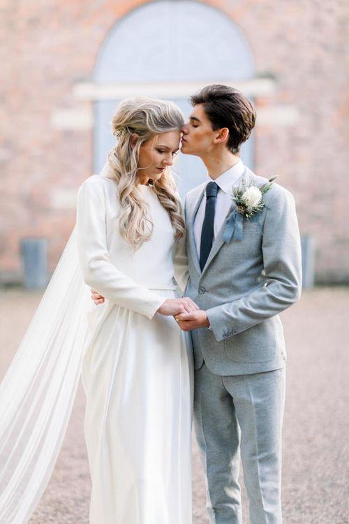 Groom in Grey Suit Kissing Brides Forehead