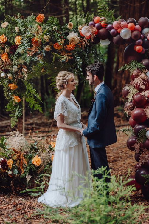 Autumnal Outdoor Wedding Reception In A Woodland // Balloon And Floral Arch For Wedding Ceremony At Patrick's Barn Woodland Industrial Wedding Venue With Grazing Board Style Food Images By Brigitte & Thierry Photography