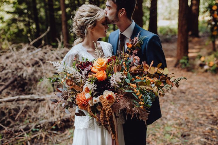 Orange, Red And Brown Autumnal Wedding Bouquet // Balloon And Floral Arch For Wedding Ceremony At Patrick's Barn Woodland Industrial Wedding Venue With Grazing Board Style Food Images By Brigitte & Thierry Photography
