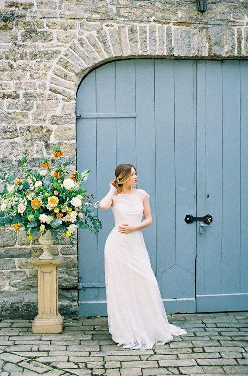 Beautiful Bride in Naomi Neoh Wedding Dress Standing Next to a  Yellow & Green Floral Arrangement