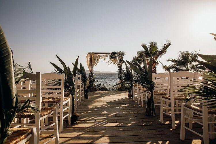 Beautiful Mykonos wedding ceremony with palm decor