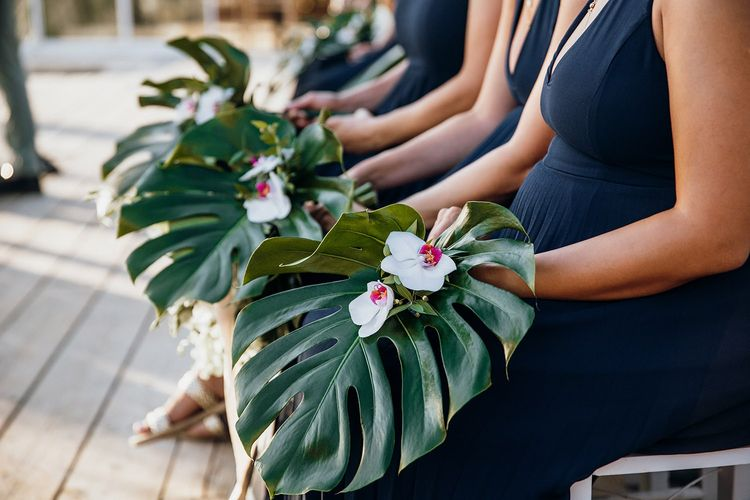 Bridesmaid hold palm leaves as alternative bouquets