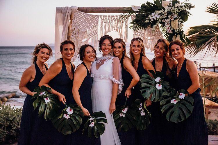 Navy blue bridesmaid dresses with palm leaf bouquet