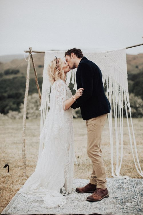 Boho Bride in Lace Rue de Seine Wedding Dress and Crown and Groom in Blazer and Chinos Kissing at the Macrame Altar