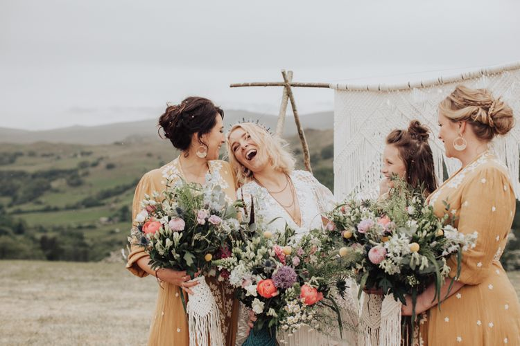 Bridal Party Holding Wildflower Bouquets Laughing Together