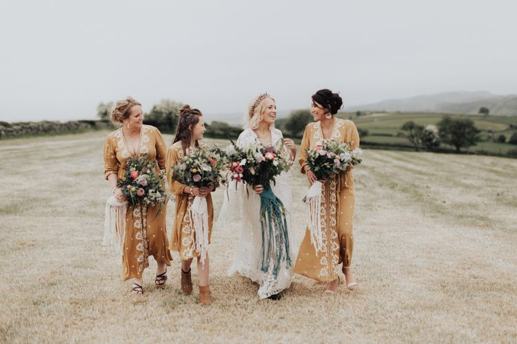 Boho Bridal Party Walking Through the Fields in Lace Rue de Seine Wedding Dress and Yellow Embroidered Dresses