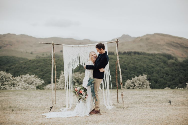 Groom in Navy Blazer and Beige Chinos Embracing His Boho Bride in a Lace Wedding Dress
