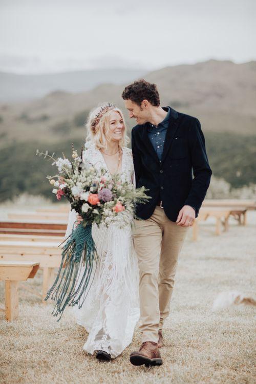 Groom in Navy Blazer and Boho Bride in Rue de Seine Wedding Dress and Crown Holding Hands