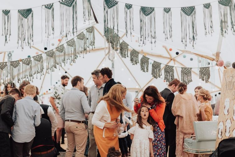 Wedding Guests Enjoying the Party in the Geodome Wedding Reception Decorated with Macrame Bunting