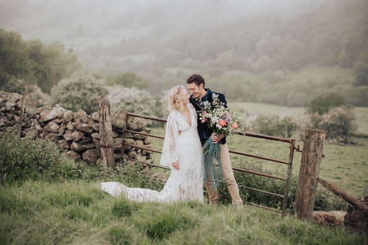 Boho Bride in Rue de Seine Wedding Dress and Groom in Chinos and Blazer Embracing in a Field