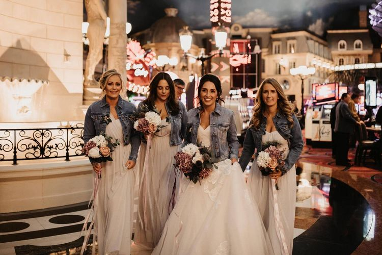 Bride and her bridal party wearing personalised denim jackets and purple faux flower arrangements