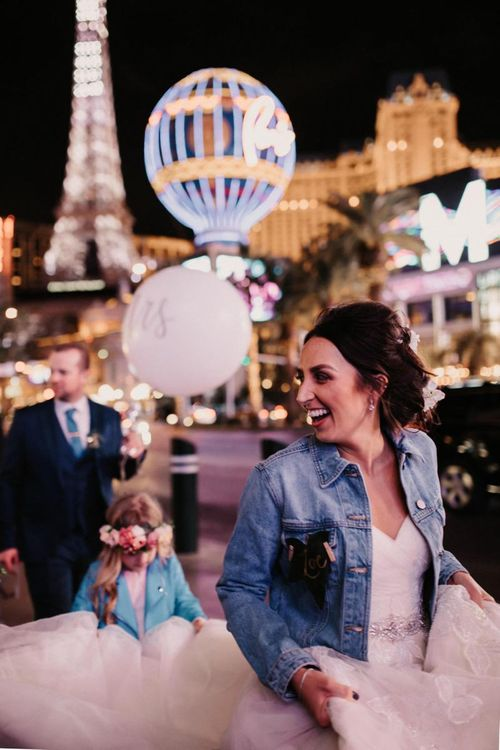 Bride wearing a personalised denim jacket taking a walk down the strip