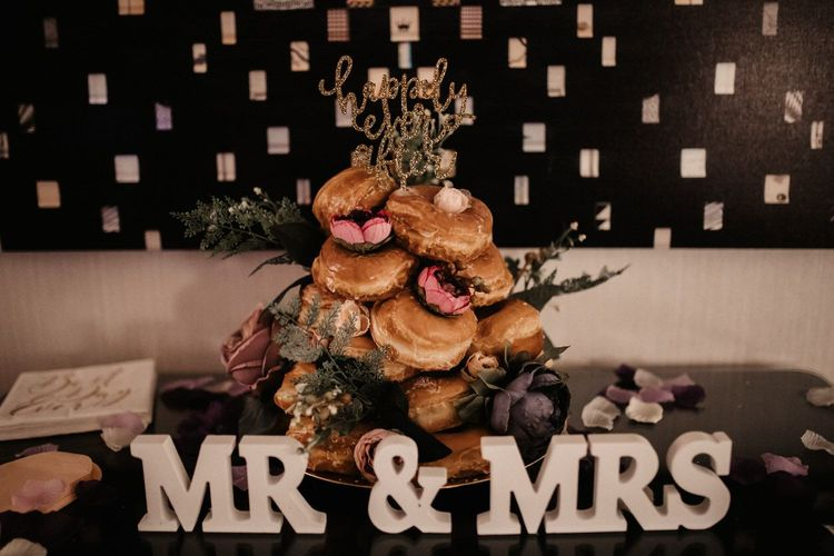 Doughnut tower with gold glitter sign and pink flower decorations