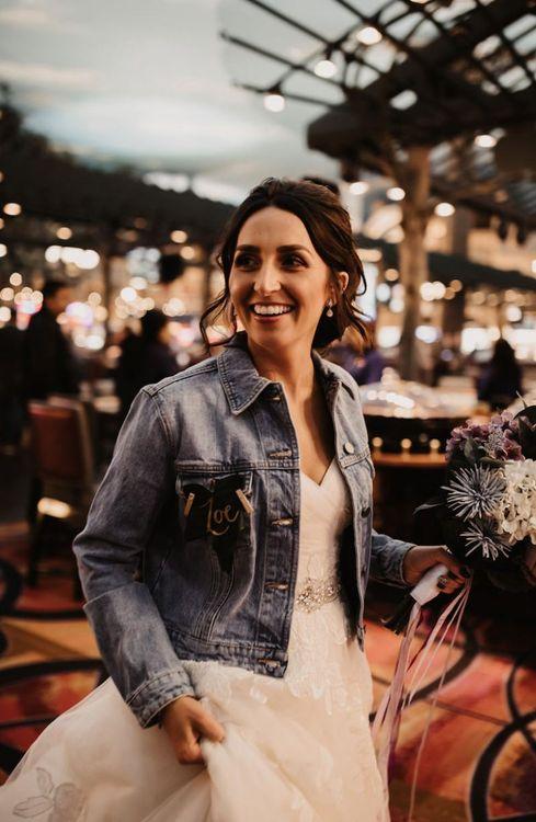 Bride wearing her personalised denim jacket and purple faux flower bouquet